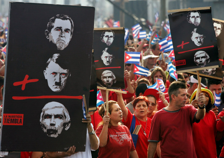 Cuban carry signs depicting US President Bush Hitler and Posada during a protest march in Havana