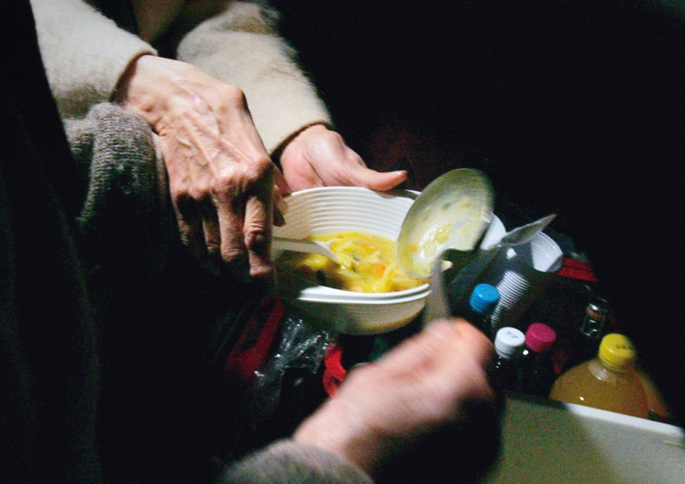 Volunteers pour pork soup into a plastic bowl during a free soup distribution to the homeless in Paris.