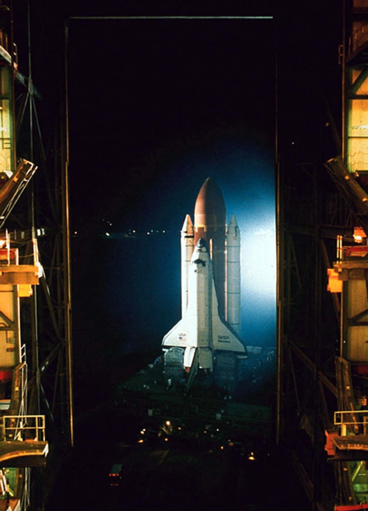 From July 1988: The space shuttle Discovery is framed by the huge doorway of the Vehicle Assembly Building as it rolls out in preparation for the first launch after the Challenger explosion. Discovery's launch came after more than two years of retooling.