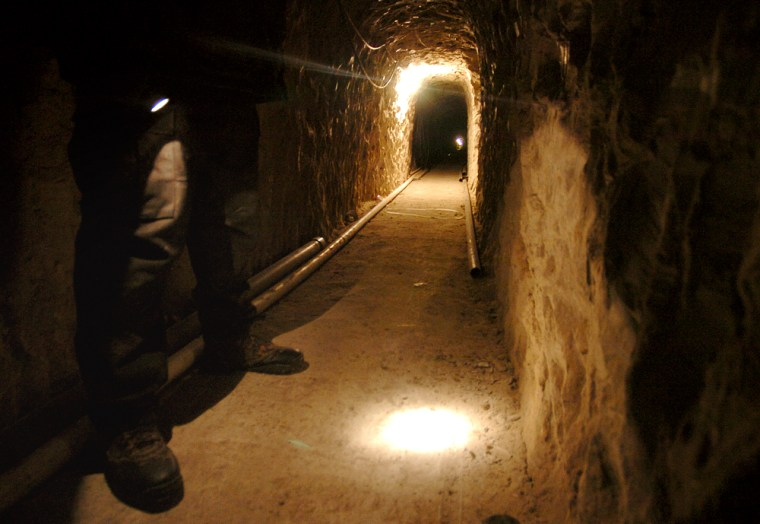 A Mexican police officer shines his flashlight in the tunnel.