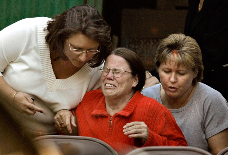 Barbara Mannis consoled at the scene of a three-vehicle crash south of Lake Butler, Fla., whereher adopted children were killed on Wednesday.