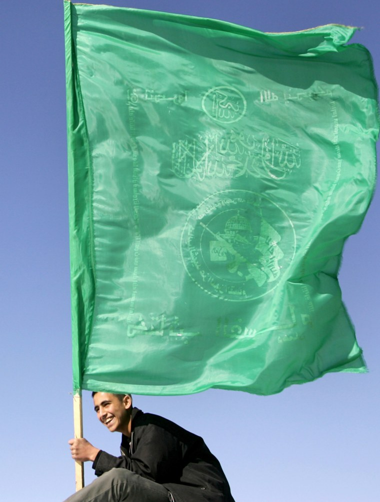 A Hamas supporter waves the movement's f