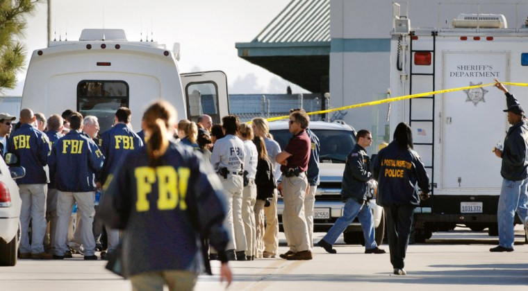 FBI investigators examine the crime scene at a parking lot and entrance of a United States Postal Service mail facility in Goleta