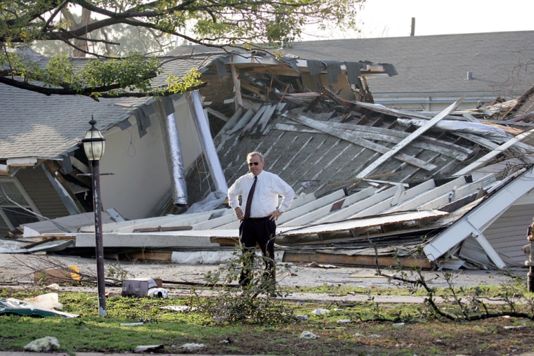 Roy Beard looks at his front yard in New Orleans Thursday morning.His home is across the street froma home that collapsed in the background from one of two twisters that hit overnight.