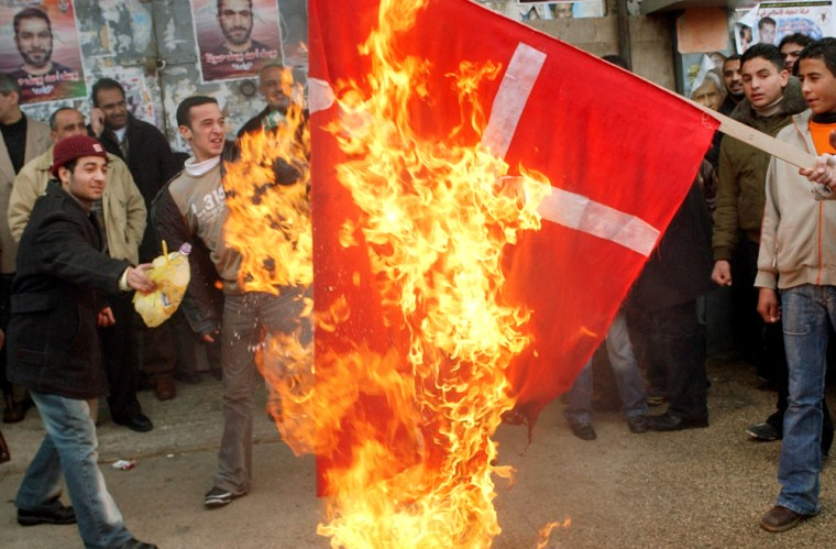 Supporters of the Islamic militant group Hamas burn a Danish flagin the West Bank town of Nablus on Friday in response to caricatures of the Prophet Muhammad that were published in European newspapers.