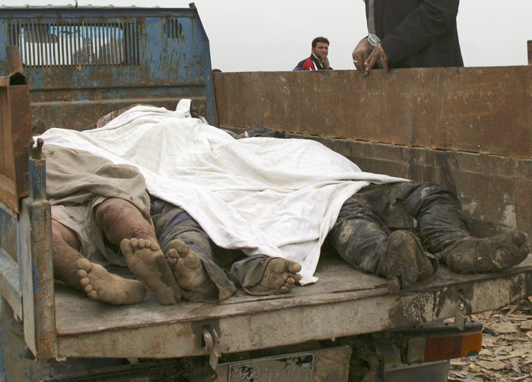 Corpses lie in a truck after they were dug from a shallow grave on the outskirts of Baghdad's Sadr city