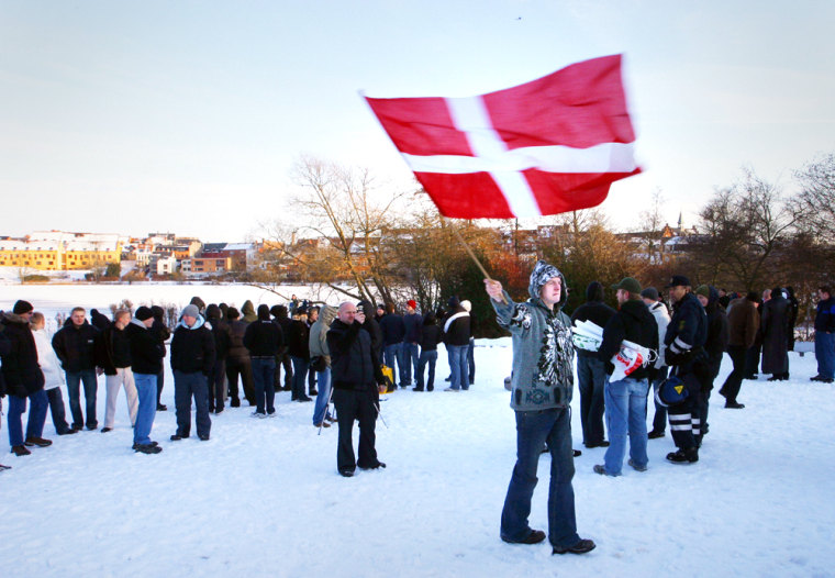 A nationalist protester waves the Danish flag in Hillerod, Denmark, on Saturday. Denmark, a small country that usually gets only cursory media attention, finds itself denounced as evil for publishing 12 cartoons of the Prophet Muhammad.