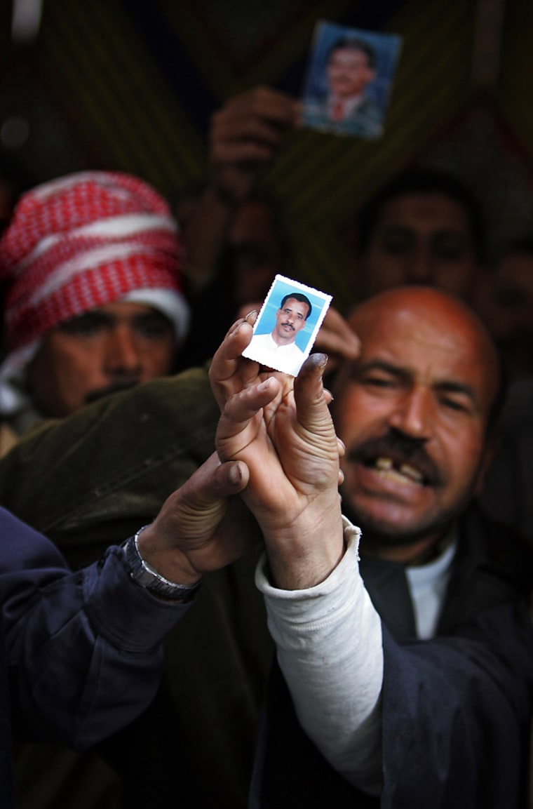 Egyptians hold up pictures of relatives missing after ferry disaster outside Red Sea port of Safaga in Cairo