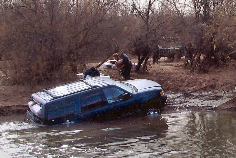 Unidentified men unload bundles of drugs from a SUV that became stuck in the Rio Grande at Neely's Crossing, east of El Paso. Men in Mexican military uniforms and armed with automatic weapons provided cover for the group, according Hudspeth County Sheriff deputies that confronted the group.