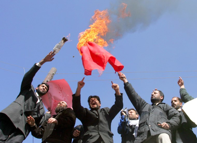 Afghan protesters burn a Danish flag in Kabul