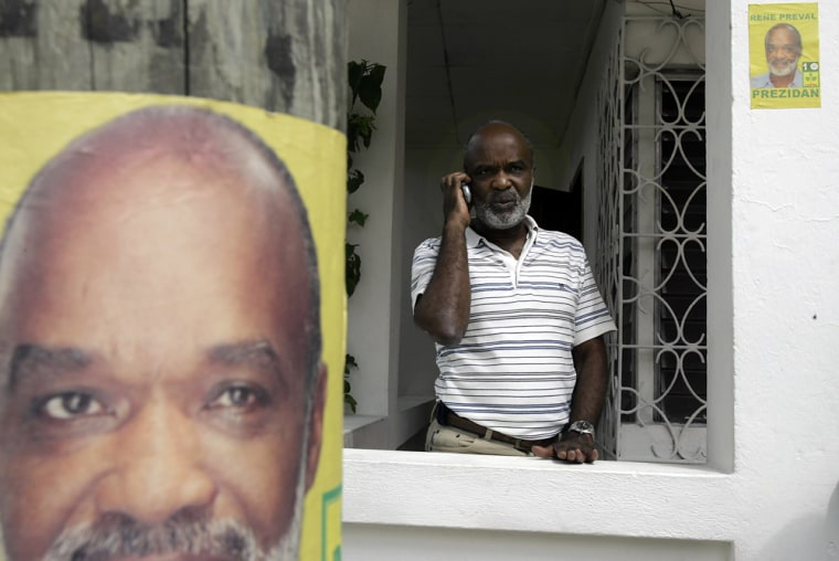 Flanked by some of his own campaign promotions, Haitian presidential candidate Rene Preval speaks on the phone Thursday outside his home in Marmelade, Haiti.