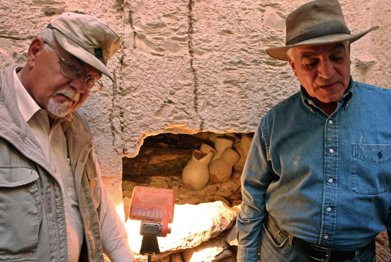 Egyptian Chief of Antiquities Hawass and head of the University of Memphis mission Schaden stand in front of a whole that opens into a newly discovered tomb in Luxor