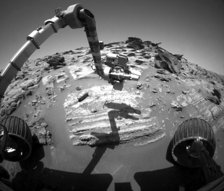A wide-angle view taken by the Spirit Rover's hazard avoidance camera shows the robot's instrument-laden arm being lowered to check out layered rock at Home Plate.