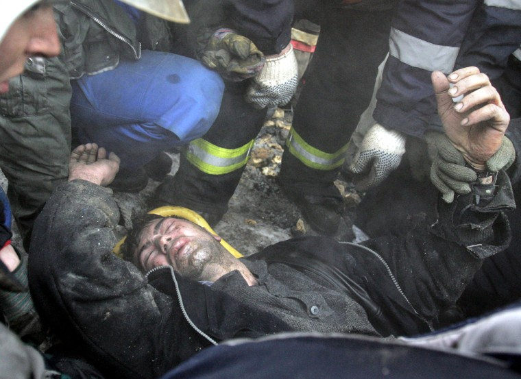 A wounded man is helped by Russian rescu