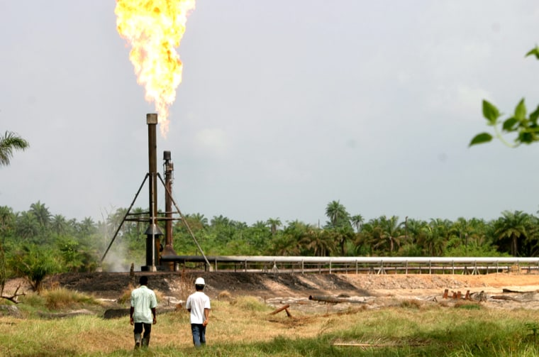 Oil workers walk at the Idu Agip flow station near Port Harcourt in Nigeria's volatile but oil-rich Niger Delta