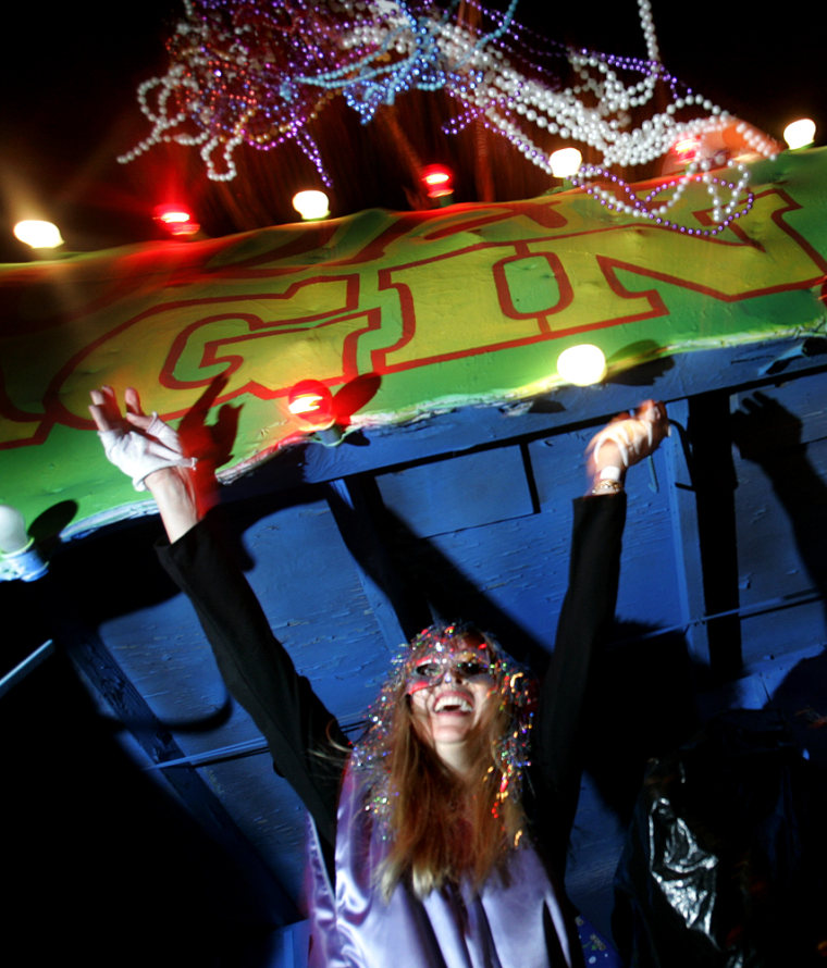A member of the Muses Krewe throws beads to onlookers as the all-female group paraded down St. Charles St. in New Orleans on Thursday night with 25 floats in tow.