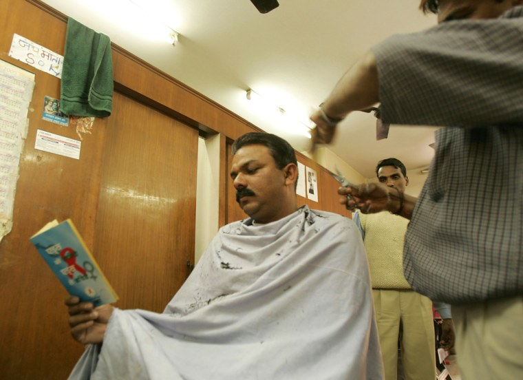 A customer reads an AIDS awareness booklet during a haircut in New Delhi, India.With more than 5 million HIV-positive people, the second highest in the world after South Africa, health activists in India are anxious that prevention messages should reach the widest possible audience.