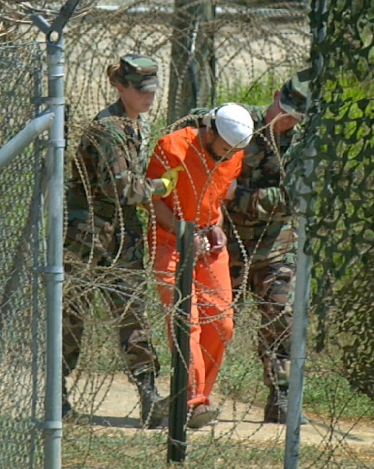 A detainee is escorted to interrogation by U.S. military guards at Guantanamo Bay, Cuba, in this2002 file photo. After four years of secrecy, the Pentagon released documents Friday that contain the names of hundreds of detainees held at the U.S. military prison.