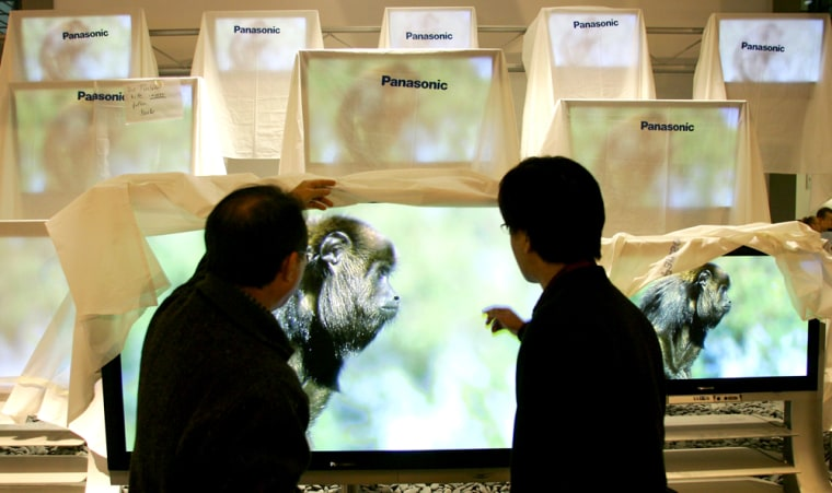 Technicians check flat screens on the booth of Panasonic at the CeBIT computer fair in Hanover