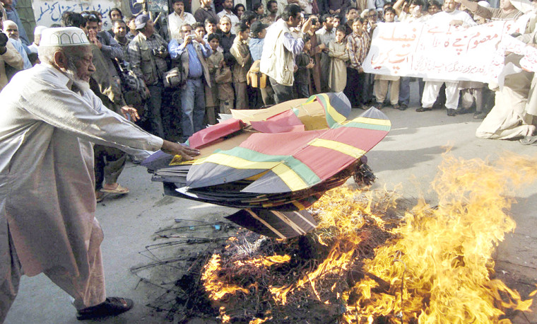 Pakistani protesters burn kites during a