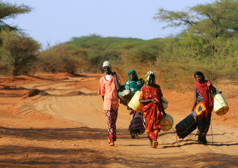 Kenyans with plastic containers search for water along road in Wajir northeastern Kenya