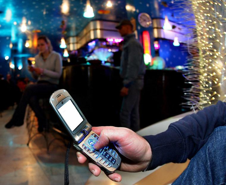 Man keys in message onto mobile phone in Milan bar