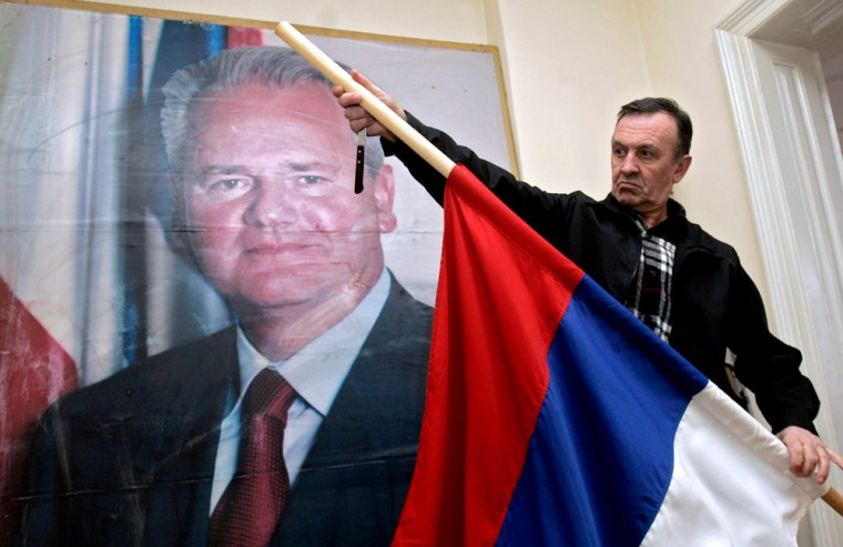 """An activist of a Slobodan Milosevic support group, """"Freedom,"""" flag to half staff in front of a poster of the former <a href=http://msnbc.msn.com/id/12083338/>Yugoslav leader at the group's</a> headquarters in Belgrade, on Saturday."""
