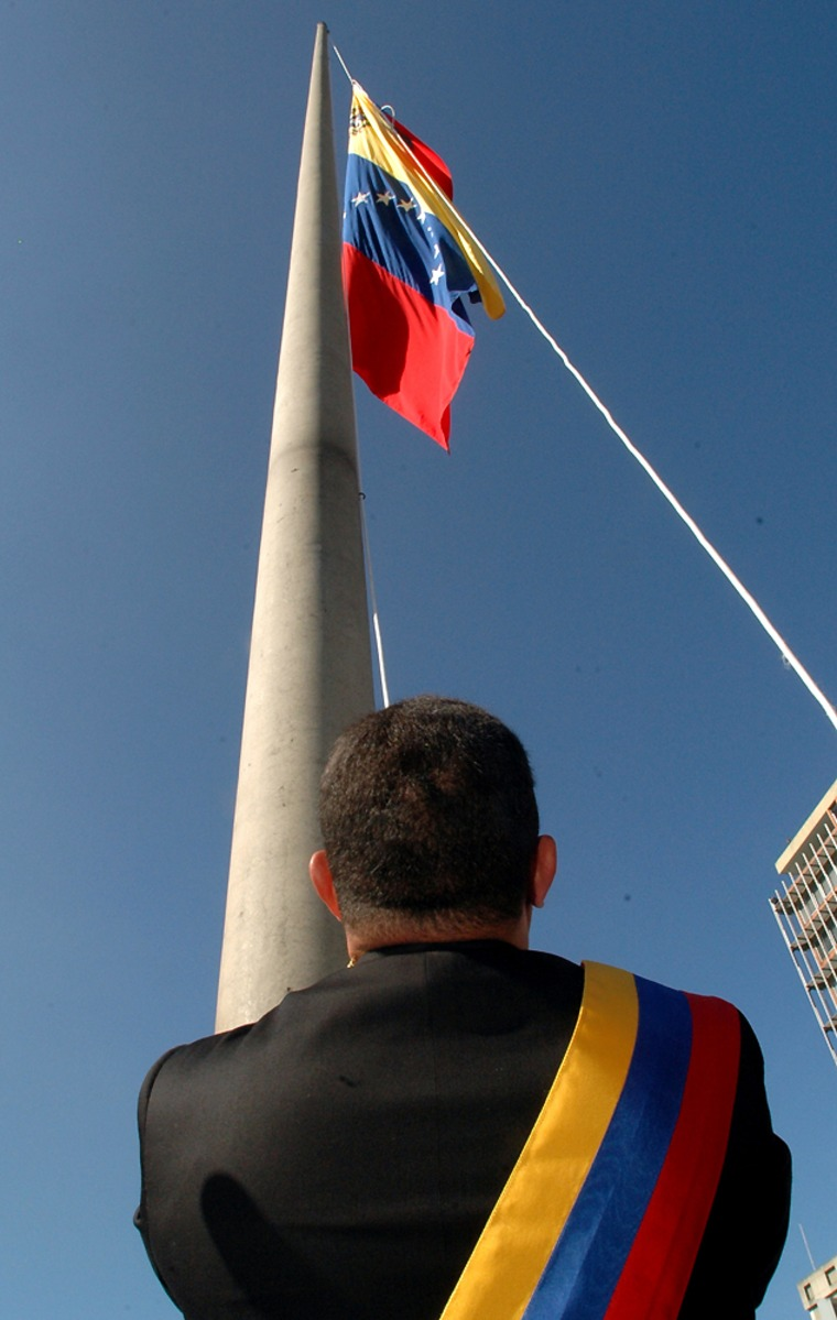 Venezuelan President Hugo Chavez raises his country's new flag at a Sunday ceremony at the National Pantheon in Caracas, Venezuela. The flag has garnered reaction, not all of it favorable.