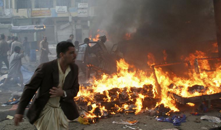 Man runs past burning debris at market after series of bomb attacks in Baghdad's Sad'r city