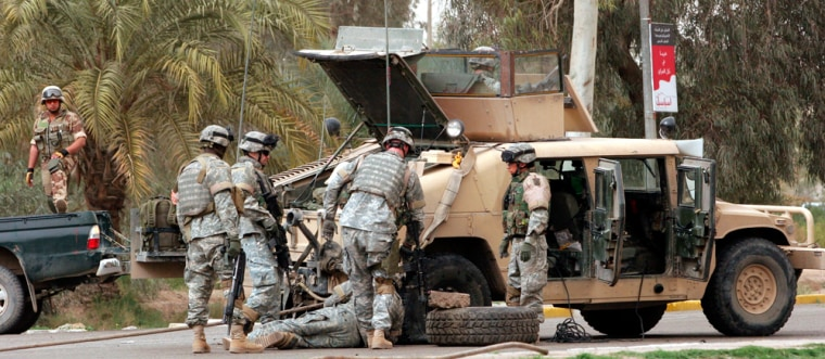 U.S. soldiers change the punctured tire of their Humvee after it ran over the pieces of a car bomb explosion in Baghdadon March 9. Humvees have become more and more laden with armor as the conflict has progressed.
