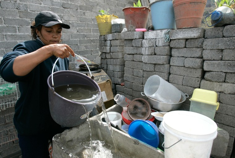 After waiting for five hours at a water distribution center to get her weekly ration, Raquel Villanueva prepares to wash her dishes at her home in Mexico City on March 9.