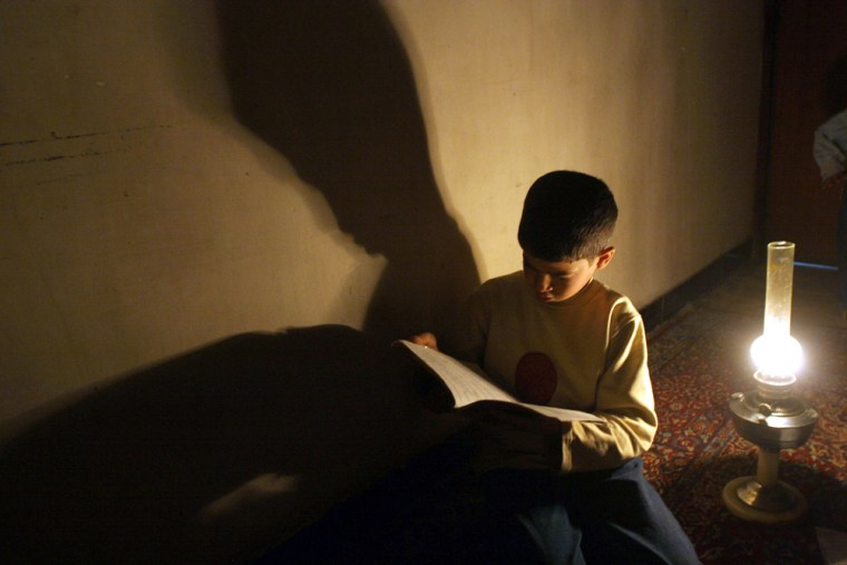 An Iraqi boy studies under an oil lamp in Baghdad, Iraq, onMarch 2. Electricity output has reached its lowest point and U.S. engineers are ending their work on the crippled power grid.