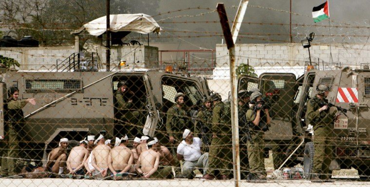 Israeli soldiers guard Palestinian prisoners as smoke billows from the prison during an army raid in the West Bank town of Jericho on Tuesday.
