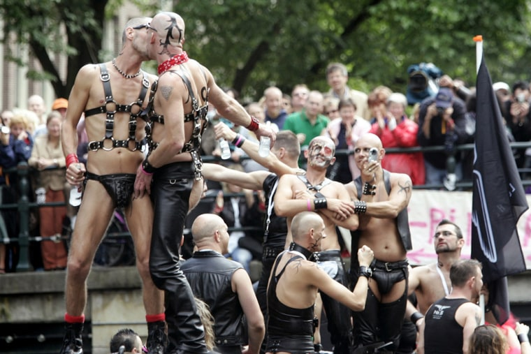 Participants kiss during Amsterdam's Canal Parade in August.Would-be immigrants to the Netherlands must watch a filmthat has images of gay men kissing and topless women on the beach.