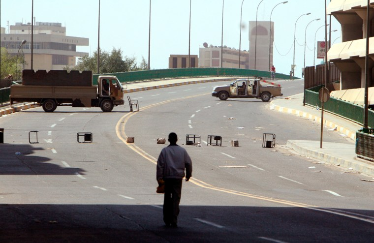 Iraqi army soldiers in vehicles guard a street during a car ban aimed at preventing bombings during parliament's swearing-in, on Thursday, in Baghdad.