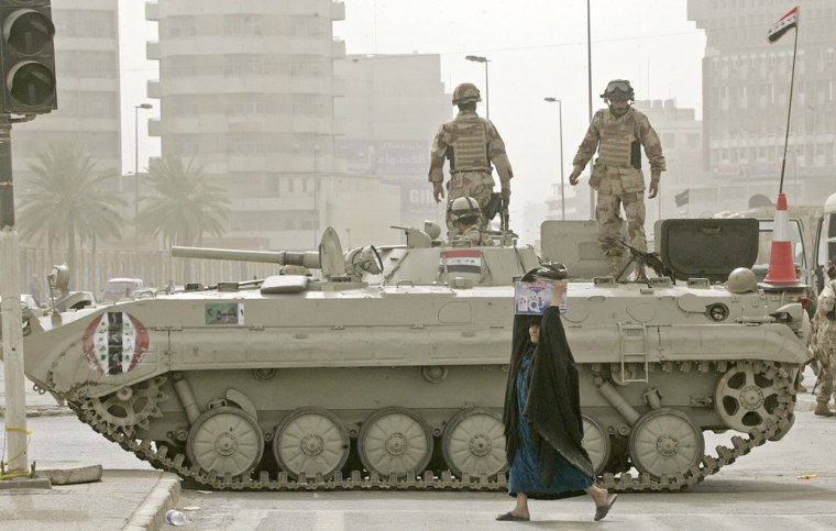 An Iraqi woman crosses a street in front