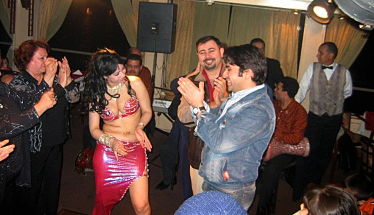 Iraqi tourists are entertained by a belly dancer while cruising on a boat party on the Nile River in Cairo, Egypt, in February.