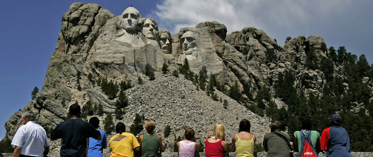 Visitors watch while workers wash Mount Rushmore inJuly. A few groups have called for a tourism boycott after South Dakota passed the nation's most stringent abortion ban.