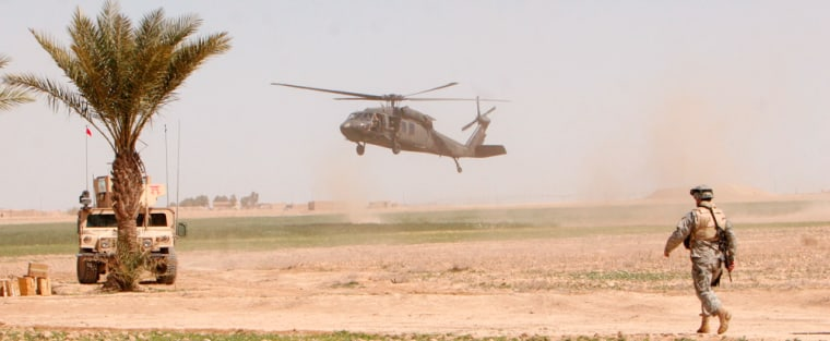 A U.S. helicopter lands as a U.S. soldier stands guard outside Samarra, Iraq, Friday, during Operation Swarmer.