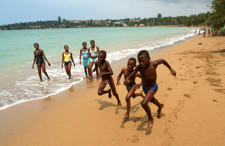 Children run on the beach as people look on at Sao Tome, Sao Tome and Principe, July, 18, 2005. The tranquil scene is one of many to be had in palm-fringed Sao Tome and Principe, a remote pair of volcanic islands smack dab on the equator whose attraction lies in what this undeveloped corner of the world lacks: No mass tourism. No traffic. No terrorism.