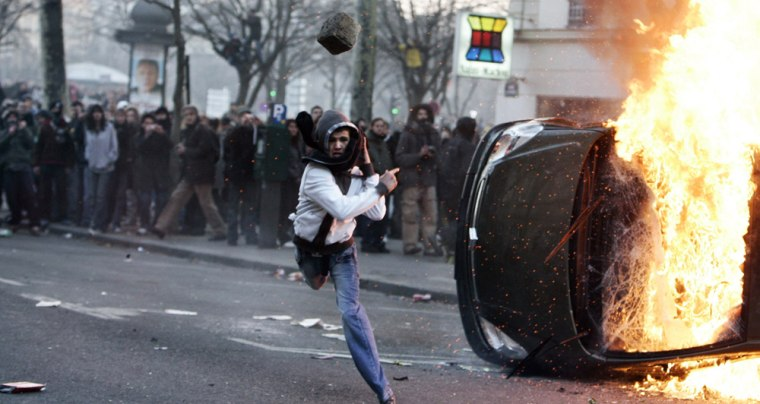 A young man trows a stone towards police