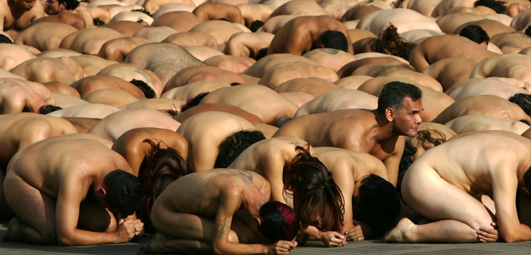 Nude volunteers prepare to pose for a photograph by American artist Spencer Tunick in downtown Caracas on Sunday.