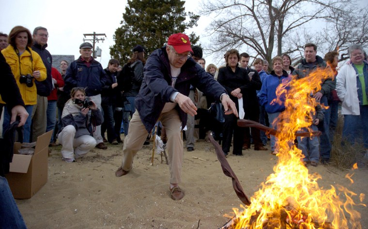 A man tosses his socks into a fire during a ceremony signifying it will soon be warm enough to slide bare feet into boating shoes, Monday in Annapolis, Md.