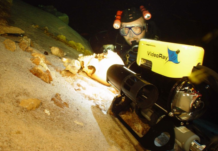 Biologist Tom Iliffe of Texas A&M University studies a centuries-oldhuman skull found in the submerged cave systems of the Yucatán during an expedition. The skull may have come from the victim of a sacrifice to the Mayan rain god.