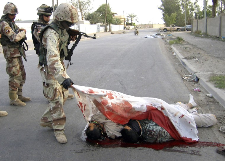 Iraqi soldier covers bodies of men found shot on street in Baghdad