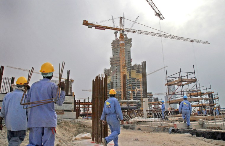 Some of the 2,500 workers on the emerging Burj Dubai tower and surrounding housing developments, background, mill in the shadows of the gray concrete tower, now 36 stories tall, in Dubai, United Arab Emirates, on Wednesday.