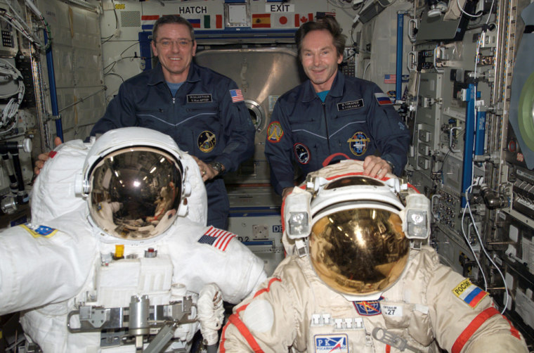 """Station commander Bill McArthur and Russian cosmonaut Valery Tokarev stand behind NASA and Russian suits for spacewalks. For a time, equipment concerns left the station in a """"no-go"""" condition for spacewalks, but NASA has come up with a contingency plan."""