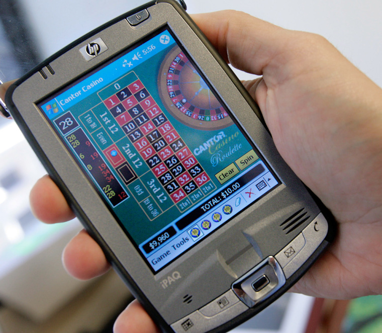 Joseph Asher, managing director of Cantor G&W, holds an HP PDA with a roulette wheel program, one of many gambling programs available, June, 2005