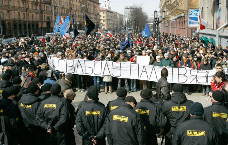 """Riot police confront oppositon supporters during a demonstration in Minsk, Belarus, on Saturday. The banner reads """"Freedom for political prisoners."""""""