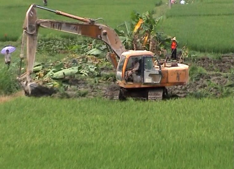 This image, taken from a DVD courtesy of Li Bai, shows contruction vehicles destroying farmland in the town Aoshi to make room for development.